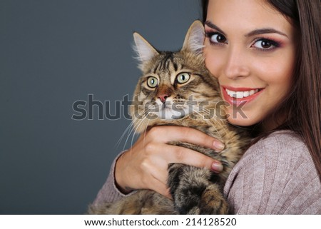 Beautiful young woman holding cat on gray background - stock photo