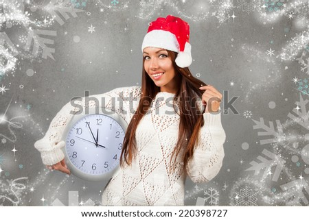 beautiful young woman holding clock wich are displaying 5 minutes to midnight