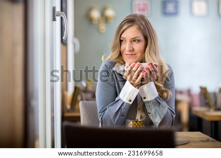 Beautiful young woman holding coffee cup while looking away at table - stock photo