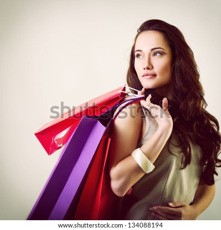 beautiful young woman holding colored shopping bags, toned - stock photo
