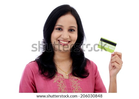 Beautiful young woman holding credit card against white background