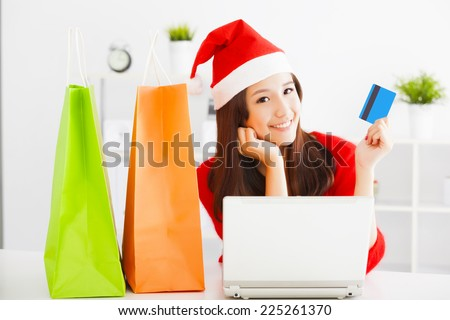 beautiful young woman holding credit card with laptop. Christmas shopping concept. - stock photo