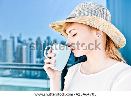 Beautiful young woman holding cup of hot coffee or tea drink in her hands in summer hat and white dress with red lipstick, Dubai city reflecting on the window glass