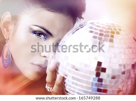 Beautiful young woman holding disco ball - stock photo