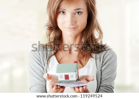 Beautiful young woman holding euros bills and house model - real estate loan concept - stock photo