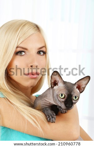 Beautiful young woman holding gray sphinx cat on light background