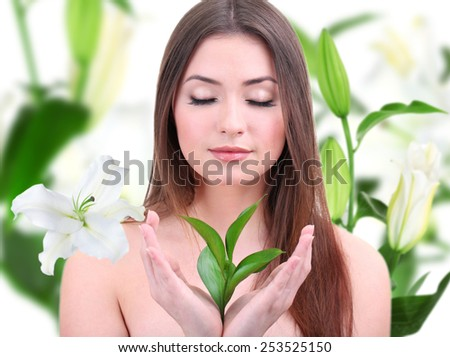 Beautiful young woman holding green leaves on lily flower background - stock photo