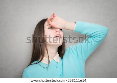 Beautiful young woman holding head in pain - stock photo