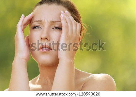 Beautiful young woman holding head in pain, against background of summer green park. - stock photo