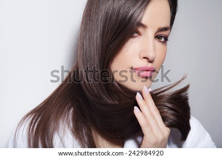 beautiful young woman holding her healthy and shiny hair, studio white - stock photo