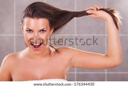 Beautiful young woman holding her long hair.