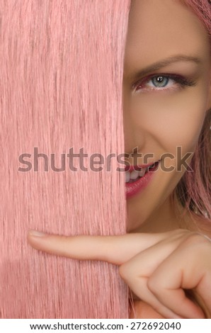 Beautiful young woman holding her pink hair - stock photo