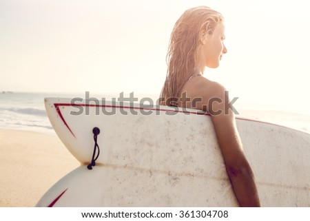 Beautiful young woman holding her surfboard after a day of surf - stock photo