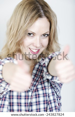 Beautiful young woman holding her thumbs up looking happy and smiling - stock photo
