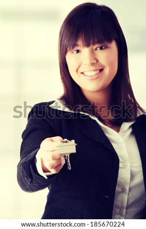 Beautiful young woman holding house keys - stock photo