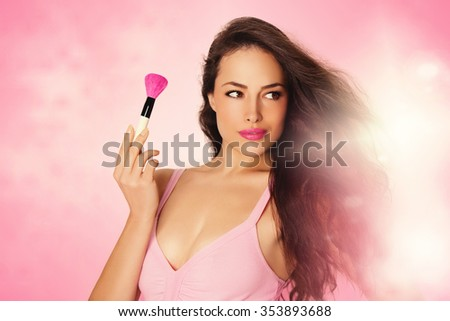 beautiful young woman holding makeup brush