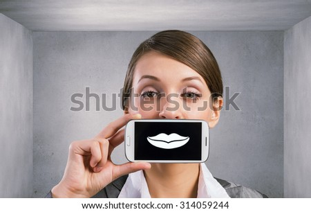 Beautiful young woman holding mobile phone against her mouth and smiling