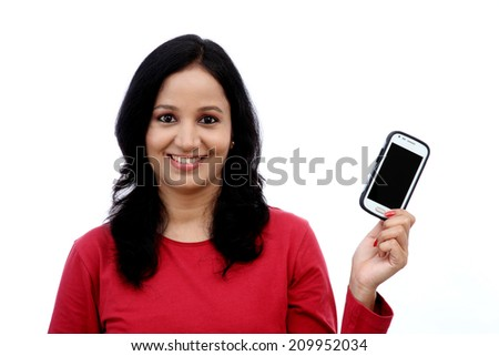 Beautiful young woman holding mobile phone against white background - stock photo