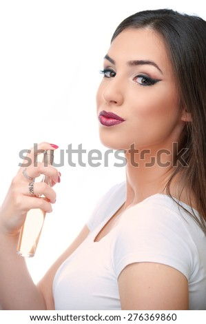 Beautiful young woman holding perfume bottle and looking into camera, isolated on white - stock photo
