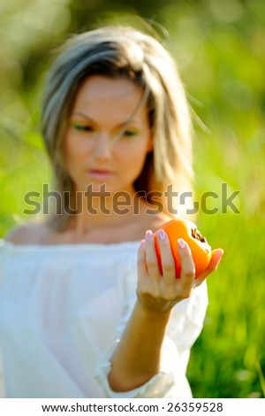 beautiful young woman holding persimmon outdoor