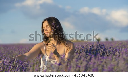 Beautiful young woman holding picking lavender flowers in the middle of a lavender field at sunset. - stock photo