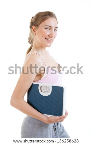 beautiful young woman holding scales - stock photo