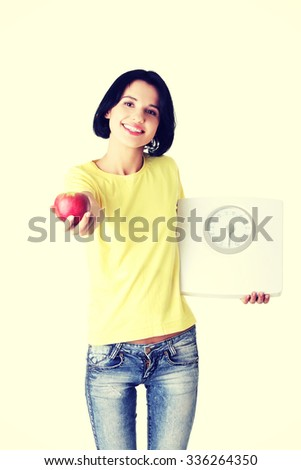 Beautiful young woman holding scales and apple - stock photo