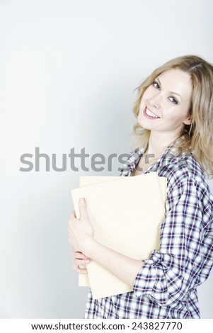 Beautiful young woman holding some folders in her arms smiling - stock photo