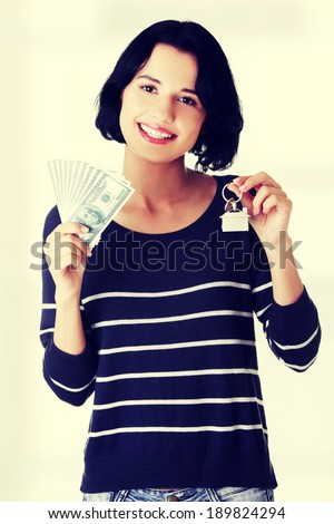Beautiful young woman holding US dollars bills and house model  - real estate loan concept - stock photo