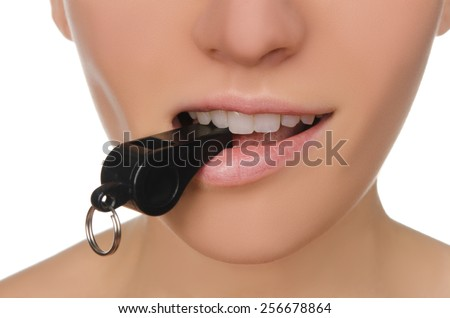 Beautiful young woman holding whistle in his mouth closeup