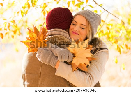 beautiful young woman hugging her boyfriend in fall - stock photo