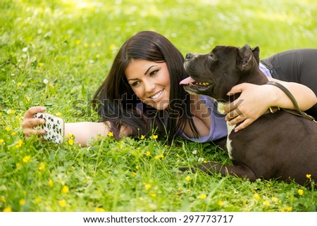 Beautiful young woman hugging her cute Stafford terrier. They lying on grass in the park and taking Self portrait on a smartphone.