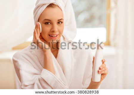 Beautiful young woman in a bathrobe with a towel on her head holding a bottle of toner and clearing her face with a sponge, looking at camera and smiling - stock photo