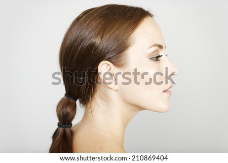 Beautiful young woman in a beauty style pose in profile view - stock photo