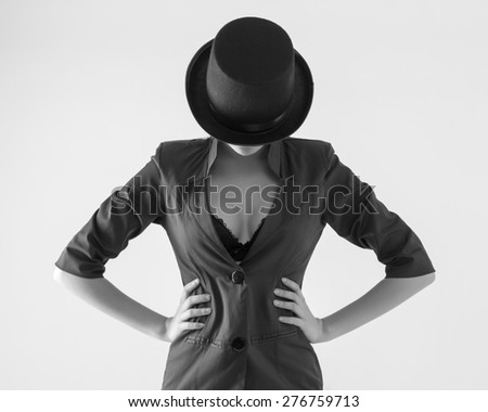 Beautiful young woman in a black hat and jacket with an open neckline.