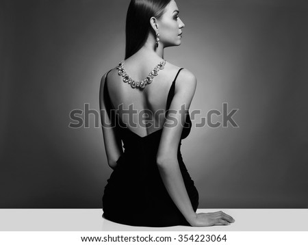 beautiful young woman in a black sexy dress.luxury.beauty brunette sitting girl Girl with a necklace on her back - stock photo