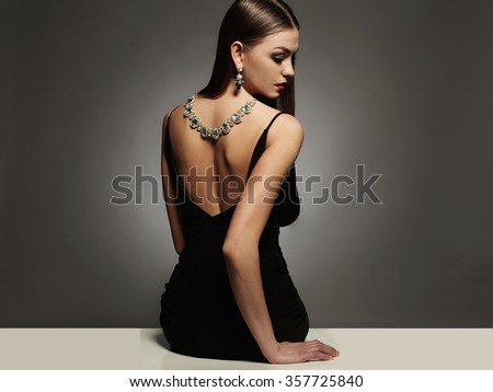 beautiful young woman in a black sexy dress.luxury beauty brunette sitting girl Girl with a necklace on her back - stock photo