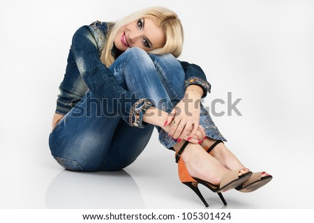Beautiful young woman in a blue denim suit sit on the floor. - stock photo