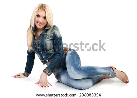 Beautiful young woman in a blue denim suit sit on the floor. Woman isolated on white background.  - stock photo