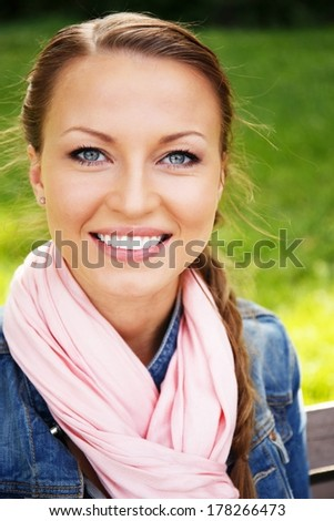 Beautiful young woman in a blue jacket and pink scarf sitting on a bench in a park