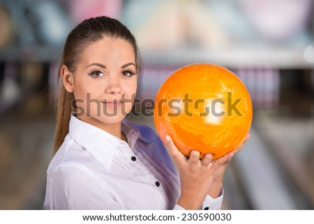 Beautiful young woman in a bowling alley is smiling and holding bowling ball.