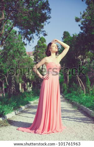 Beautiful young woman in a bright dress posing outdoors in the spring against the backdrop of the park.