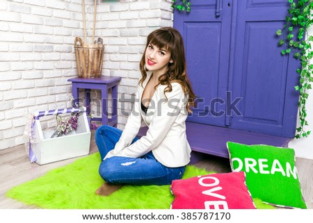 Beautiful young woman in a bright interior with flowers studio. Spring scenery.