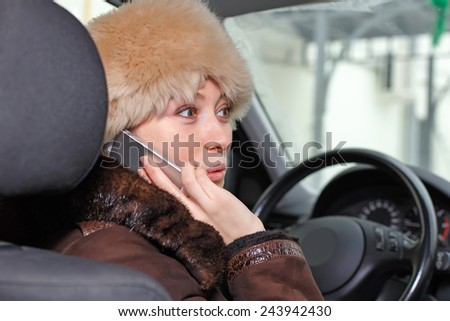 Beautiful young woman in a car talking on the phone - stock photo