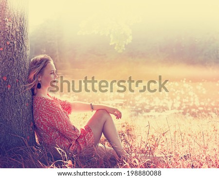 Beautiful young woman in a dress on the nature dreams - stock photo