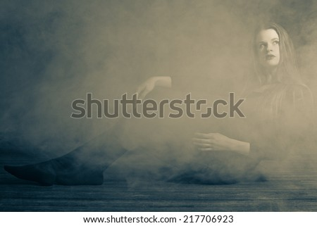 Beautiful young woman in a fog.  Low lighting and fog to give a moody feel to the image. Editing includes some noise for effect.