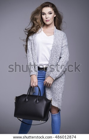Beautiful young woman in a gray sweater and a black handbag