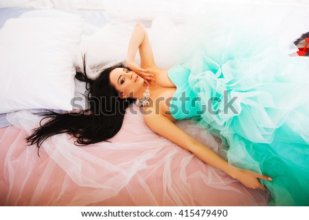 Beautiful young woman in a green dress with curly long hair, lying on the bed - stock photo