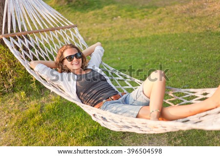 beautiful young woman in a hammock in summer - stock photo