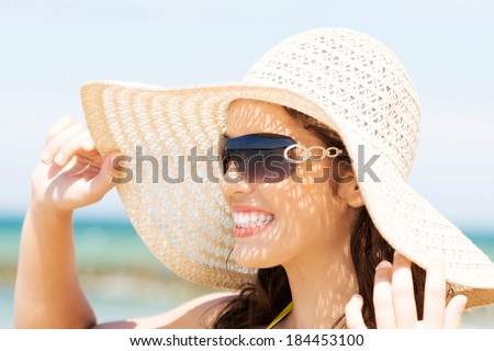 Beautiful young woman in a hat and swimsuit over seaside sunny day background. - stock photo